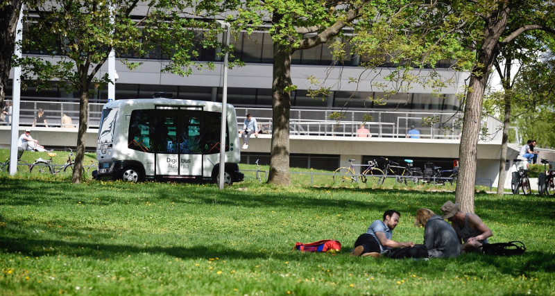 Self-driving-bus and a park with people lying in it